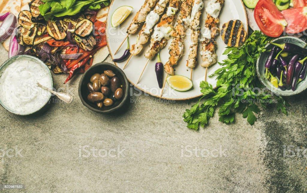 Flatlay de pinchos de pollo a la plancha, pan plano, perejil, verduras, aceitunas - foto de stock