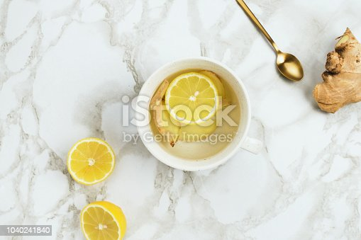 Flatlay of healthy drink with lemon and fresh ginger root on marble background, natural cold or sore throat