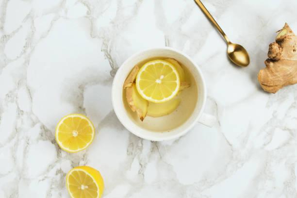 flatlay gesundes getränk mit zitrone und frische ingwerwurzel auf marmor hintergrund, natürliche kälte oder halsschmerzen - heiße zitrone stock-fotos und bilder