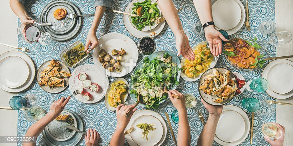 Mediterranean style family or friends dinner. Flat-lay of table with various salads, starters and pastries over blue table cloth with human hands holding glasses with drinks and sharing food, top view. Holiday gathering, celebration, vegetarian party concept