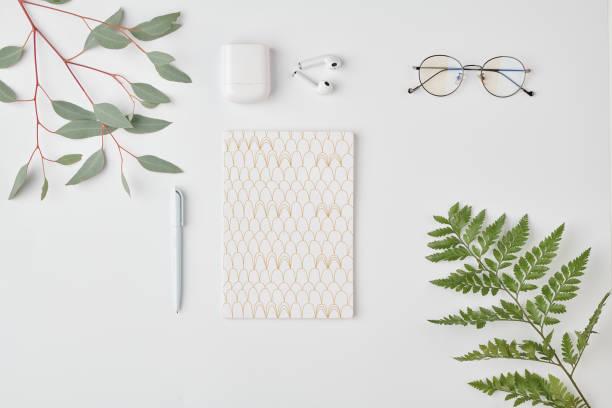 Flatlay de cuaderno con pluma, anteojos y auriculares sobre fondo blanco - foto de stock