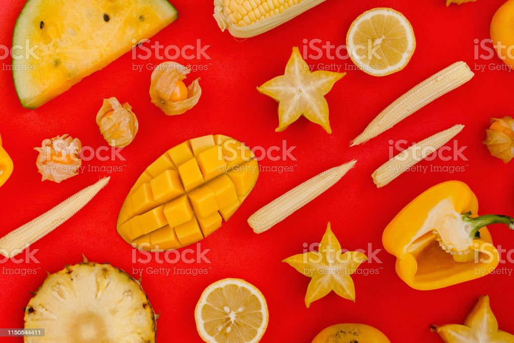 Flatlay of various yellow and orange fruits and vegetables knolled on...