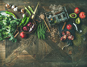 Winter vegetarian food cooking ingredients. Flat-lay of seasonal vegetables and fruit, beans, kitchen utencils over vintage wooden table background, top view, copy space. Healthy, clean eating concept