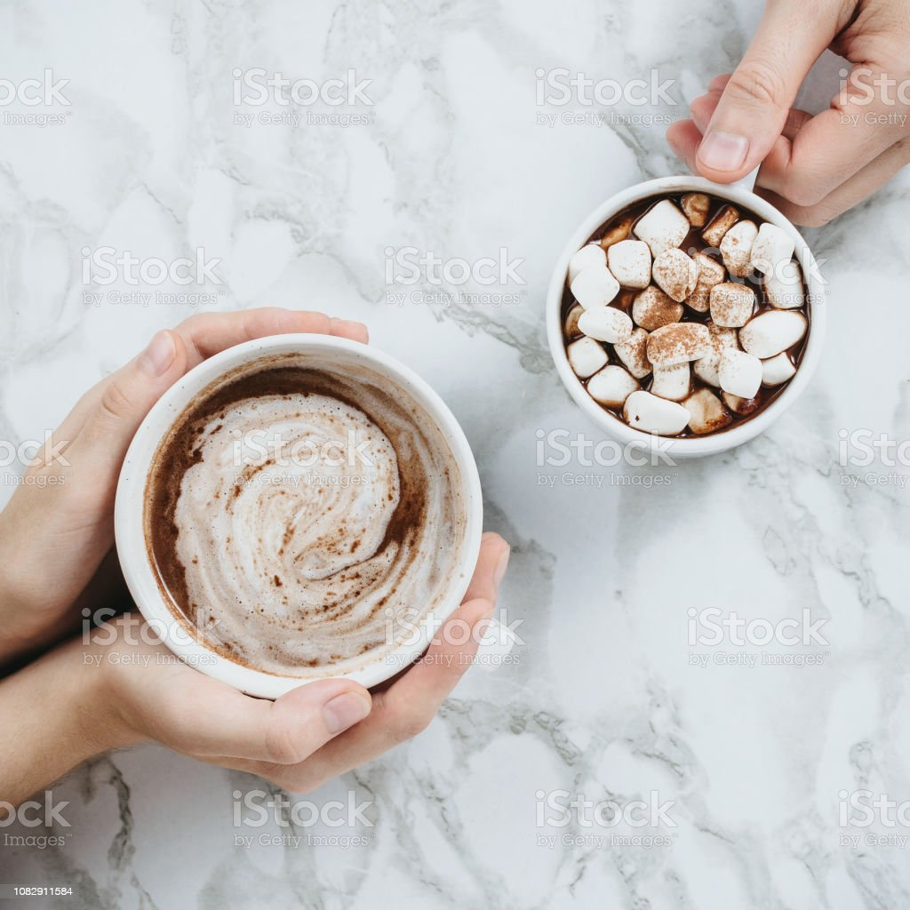 Flatlay of woman and man holding two cups of vegan cocoas on marble stock photo