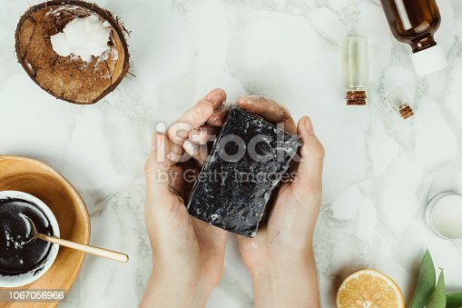 Flatlay of woman's hands holding homemade charcoal soap with its ingredients on the side, natural home beauty concept