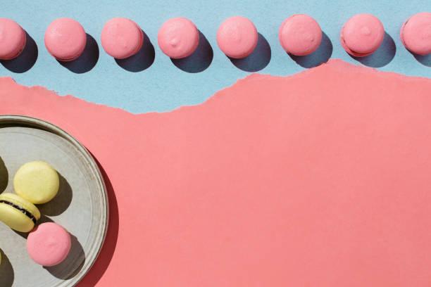 Flatlay of yellow and pink vegan macaroons on pastel stock photo