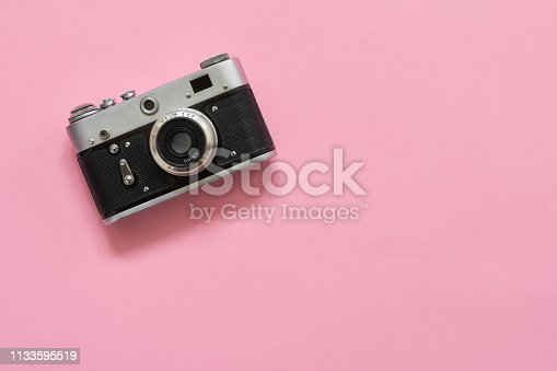 Flatlay vintage retro camera on pink background. Copy space, top view. Minimalistic concept.