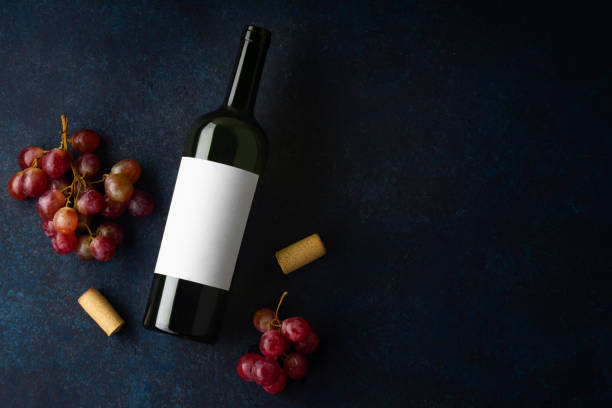 Flatlay with bottle of red wine, corks and red grapes on blue background with copy space Flatlay with bottle of red wine, corks and red grapes on blue background with copy space cabernet sauvignon grape stock pictures, royalty-free photos & images