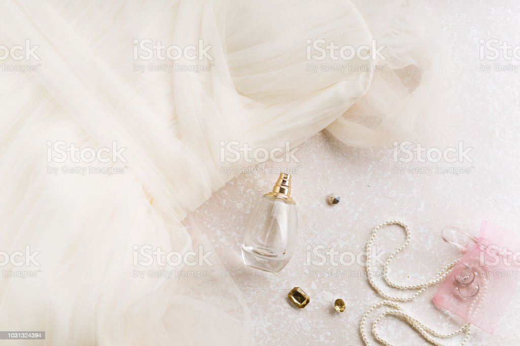 Flatlay with bridal dress and accessories on creamy pink background...