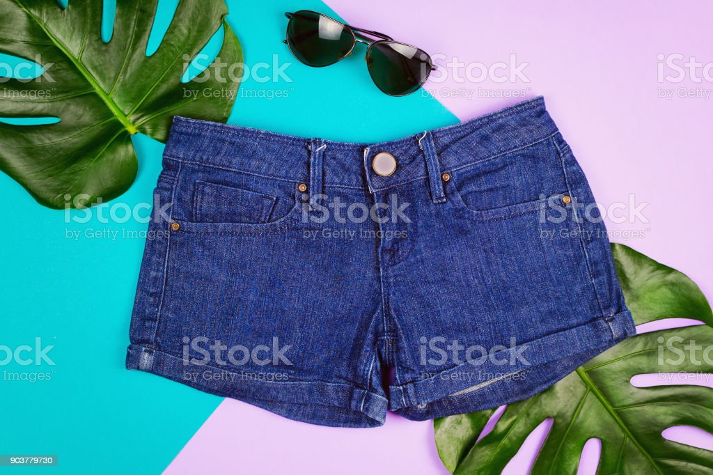 Flatlay with jeans shirts, sunglasses and monstera leaves. Summer or vacation concept. stock photo