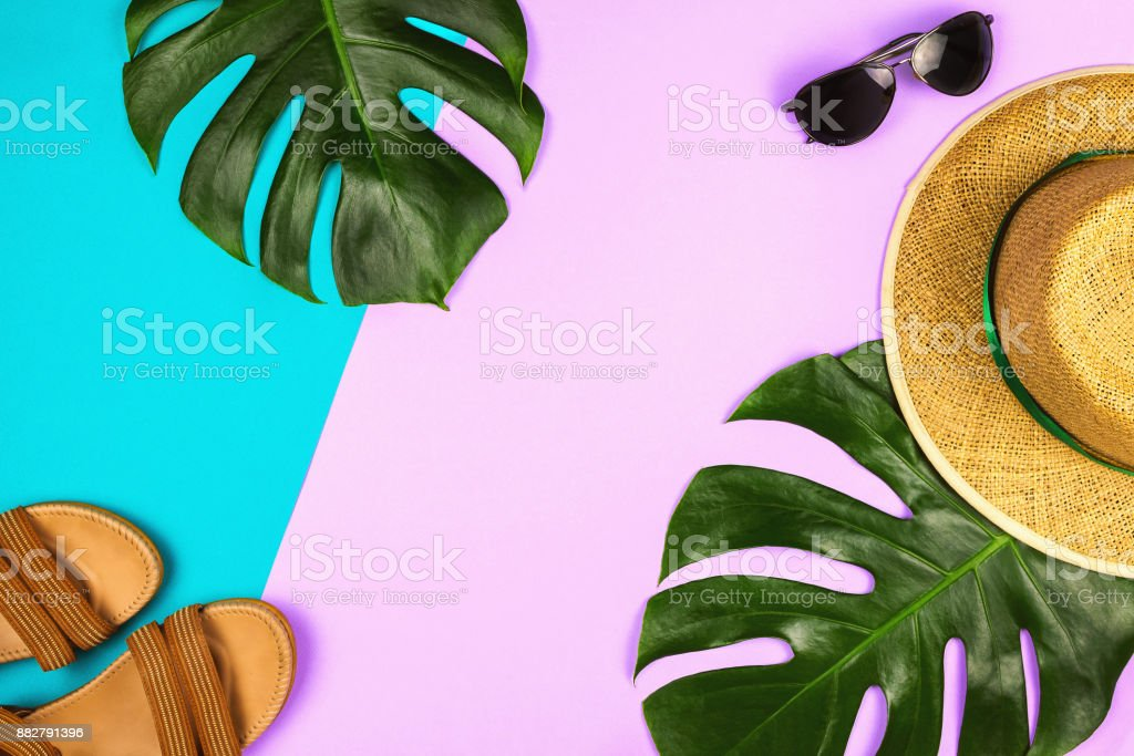 Flatlay with monstera leaves, straw hat and other accessories, summer and holiday concept, copyspace stock photo