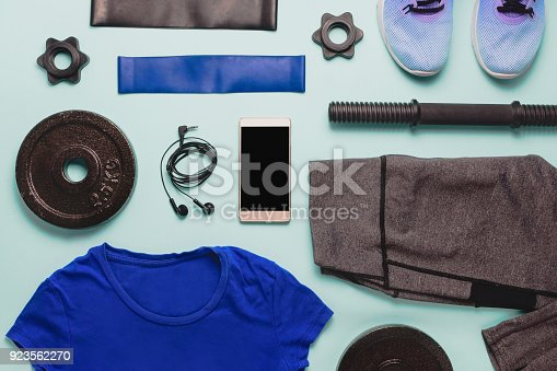Flatlay with various sport accessories: training shoes, leggins, resistance bands, weights and smart phone with black copyspace. Top view.