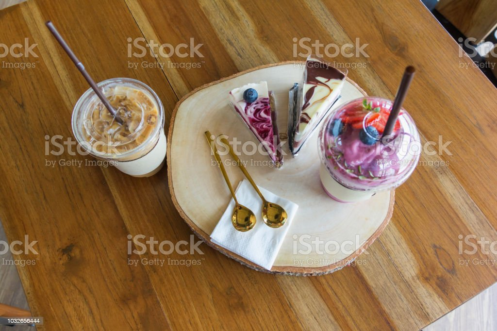 Flatlay,beverage set of iced coffee blueberry cake and smoothie in wood table at cafe stock photo