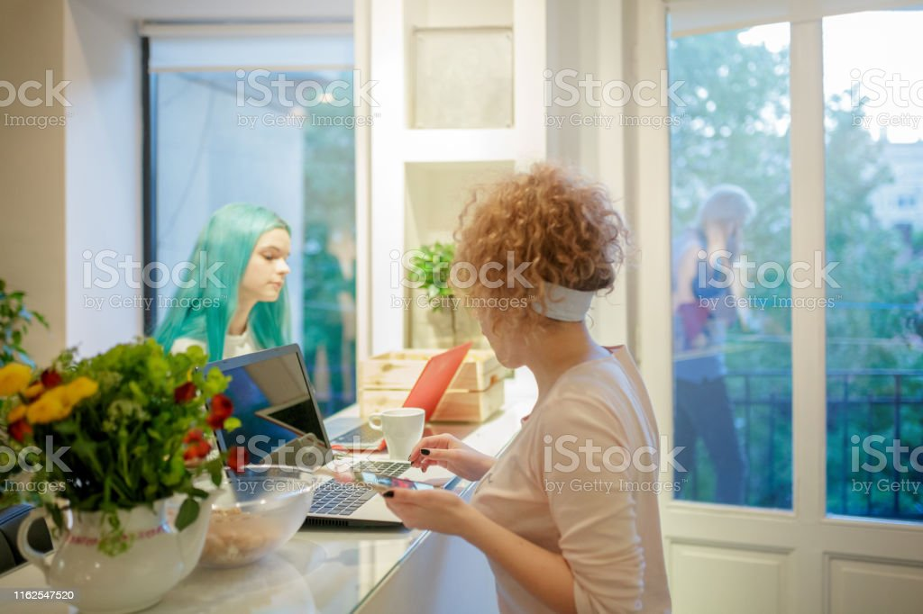 Flatmates at kitchen bar counter working at home, using laptops and...