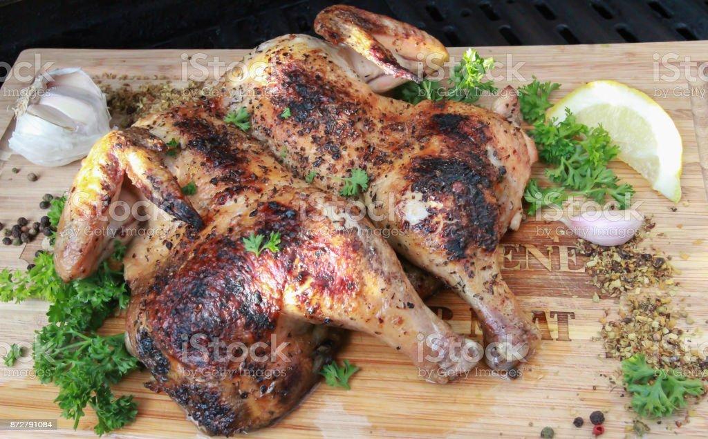Aplanado Bar B Q pollo sobre una tabla de madera con limón y perejil - foto de stock