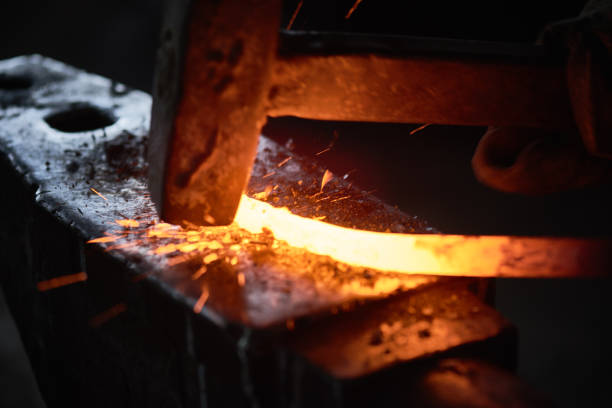 Flattening Close-up of blacksmith hitting hot metal with hammer on anvil metalwork stock pictures, royalty-free photos & images
