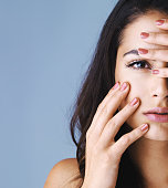 Studio shot of an attractive young woman touching her face to show off her beautiful nails against a gray background