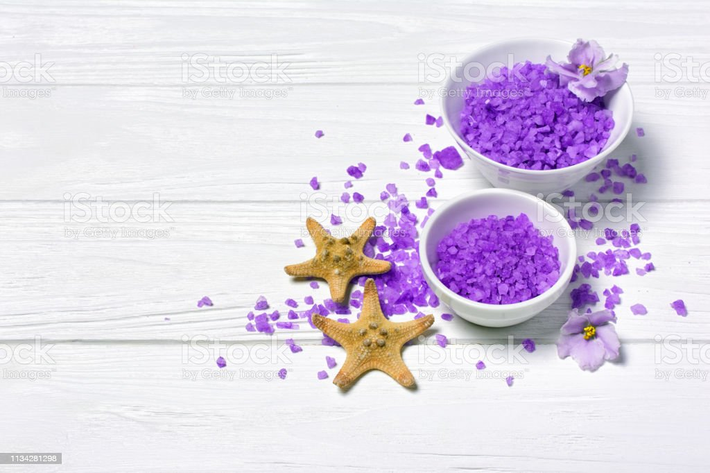 Flavored purple sea salt crystals for bath in bowls with violet...