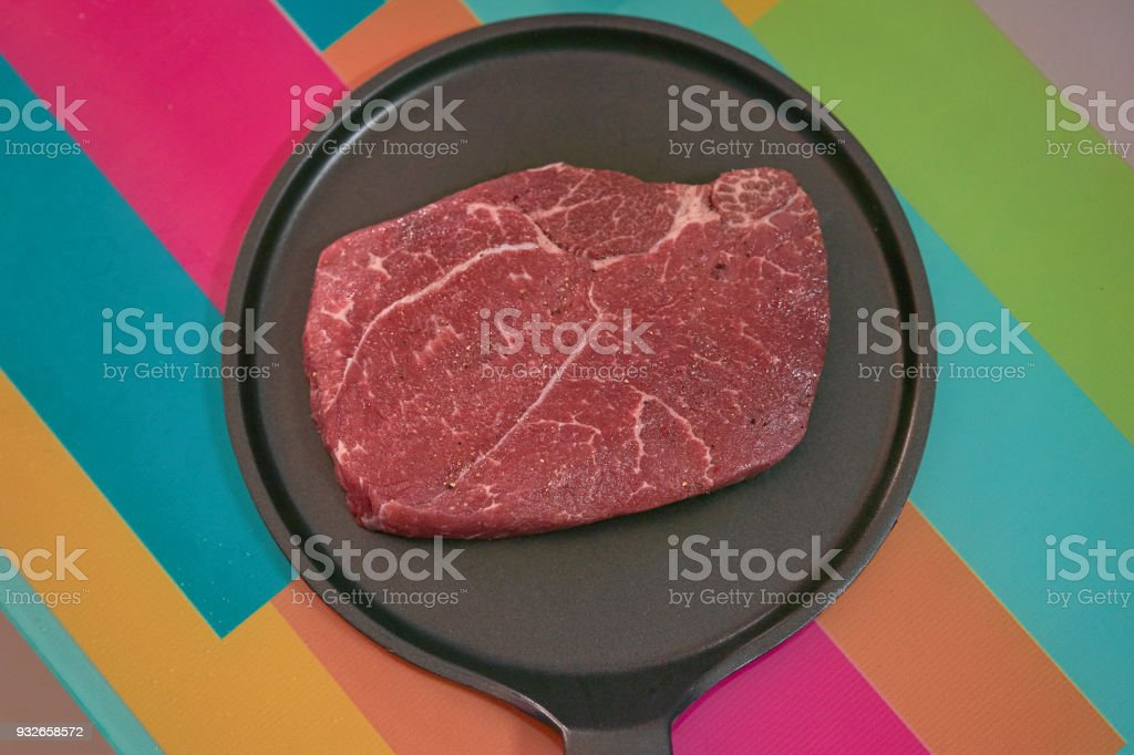 Flavored raw meat steak for cook on non stick pan on colourful table stock photo