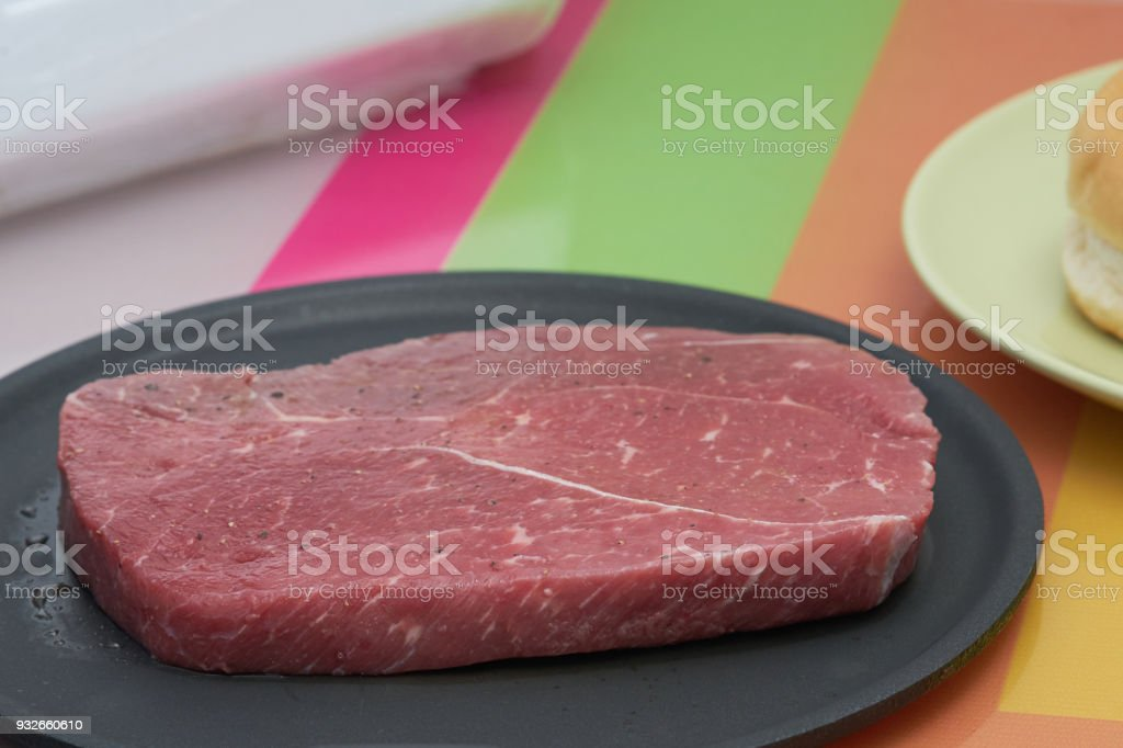 Flavored raw meat steak for cook on non stick pan with round shape or berger bread in plate on colourful table,side view stock photo