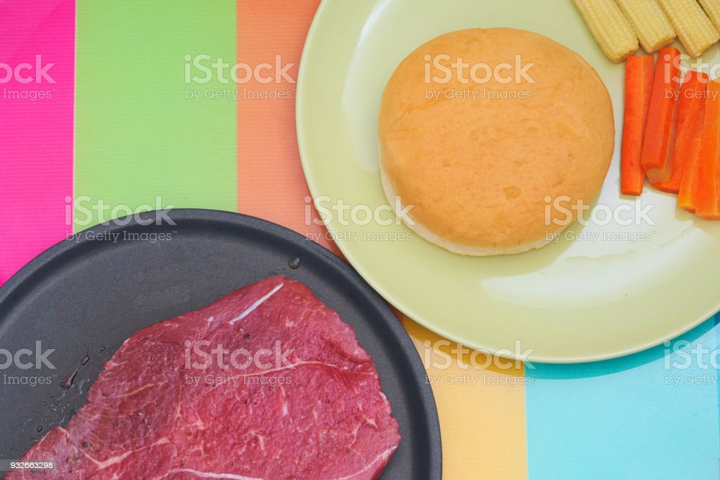 Flavored raw meat steak for cook on non stick pan with round shape or berger bread and sliced carrots with corn in plate on colourful table stock photo