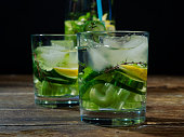 Homemade flavored iced water with cucumber, celery, lemon and thyme. Close-up. Black background