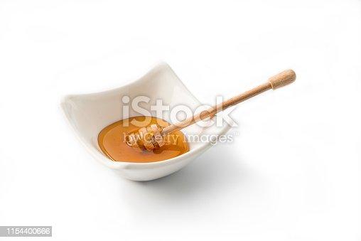 Bowl of honey isolated on white background , studio shot