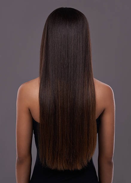 Flawless hair thanks to her trusty flat iron! Rear view of a young woman with beautiful long hair straight hair stock pictures, royalty-free photos & images