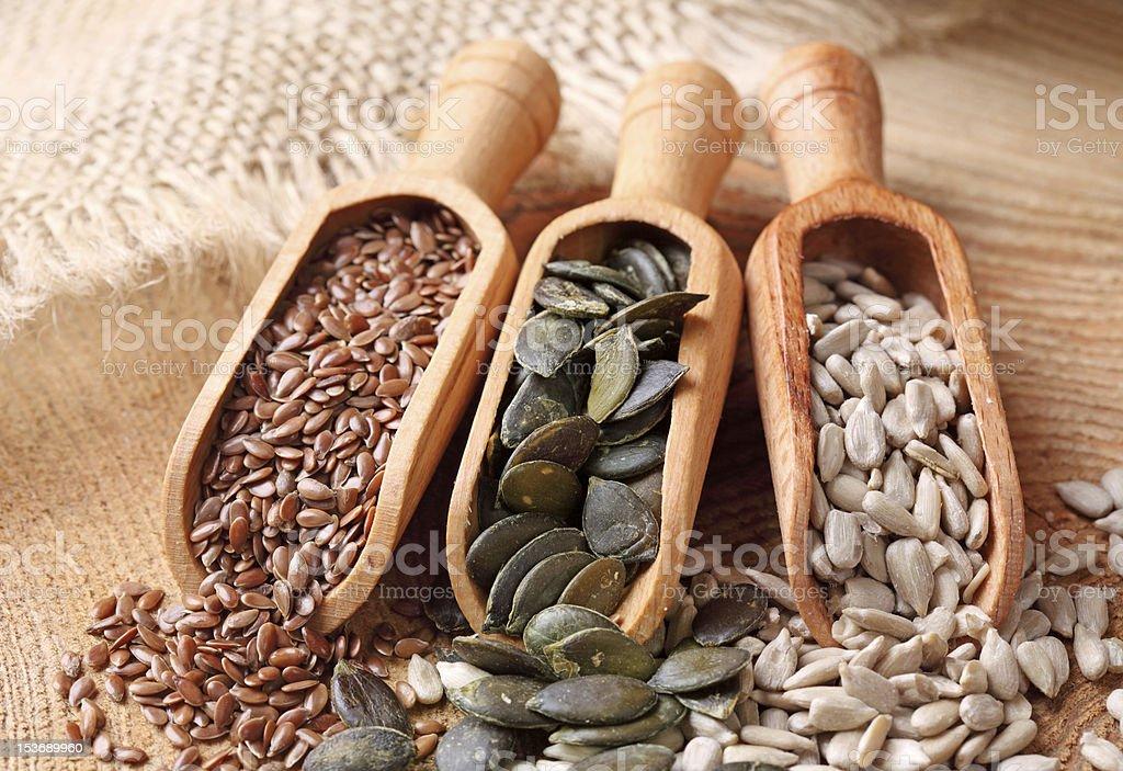 Flax, pumpkin and sunflower seeds Flax, pumpkin and sunflower seeds in wooden spoons Brown Stock Photo