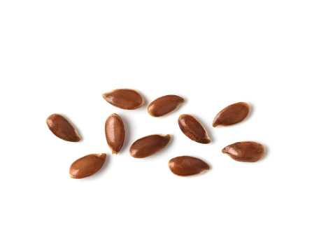 Extreme close up of flax seeds isolated on white background. Linseed pile closeup isolated on white with clipping path. Top view or flat lay. Macro shot