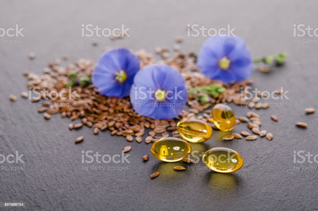 Flax seeds , beauty flower and oil in caps on a grey background. Phytotherapy. stock photo