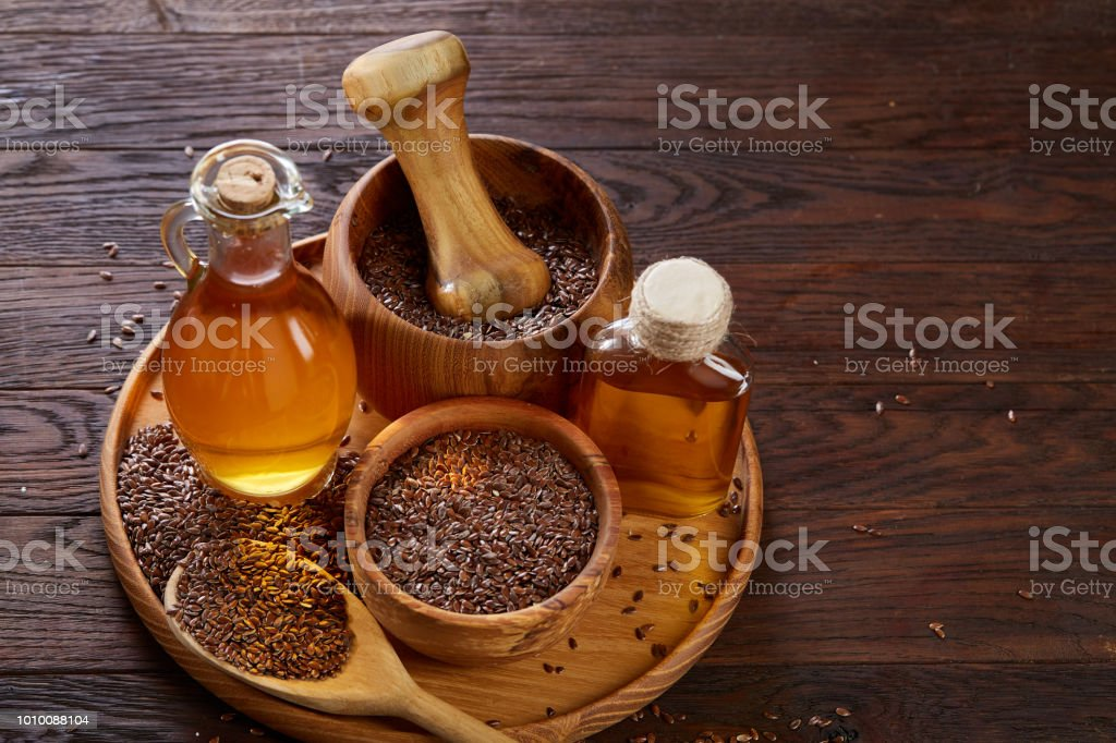 Flax Seeds In Bowl And Flaxseed Oil In Glass Bottle On Wooden