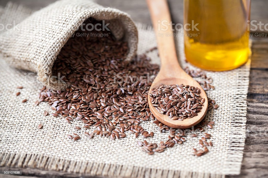 Flax seeds in the sack and oli on wooden background stock photo
