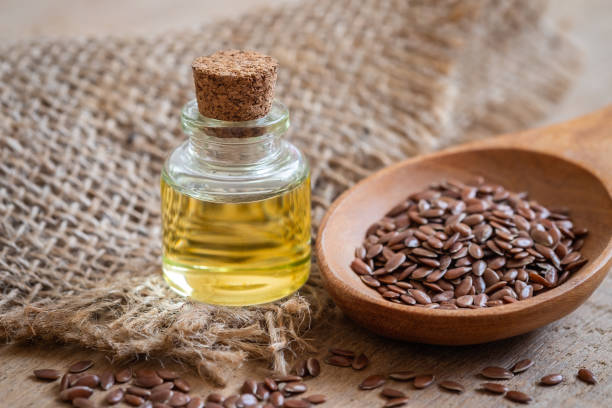 Flaxseed Oil In Bottle And Brown Flax Seeds On Wooden Spoon Stock