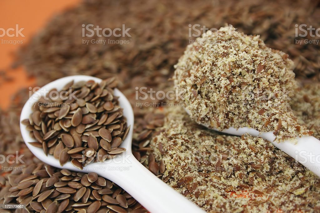 Flaxseed Whole and ground flaxseed (linseed) against an orange background. Alternative Medicine Stock Photo
