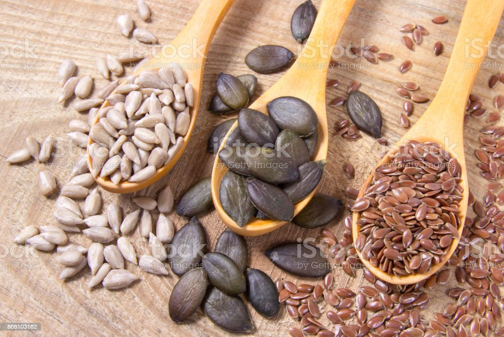 Flaxseed, pumpkin and sunflower seeds in wooden spoons. stock photo