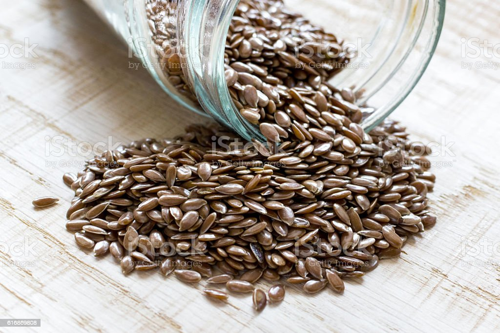 flaxseed spilled from a glass jar on a wooden board stock photo