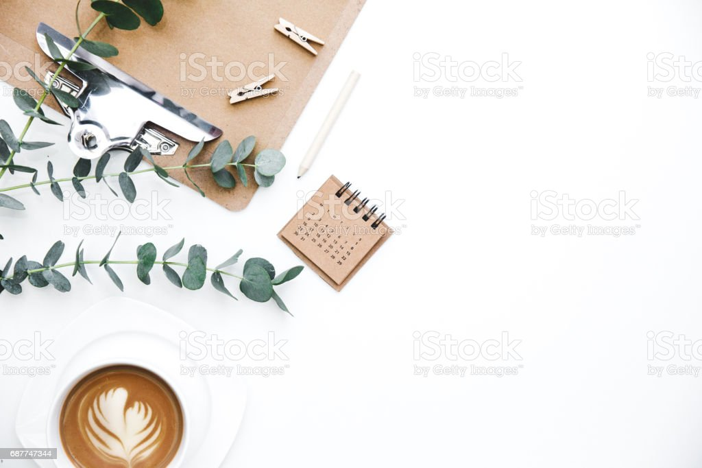 Flay lay, Top view office table desk. Feminine desk workspace frame with clipboard, green leaves eucalyptus  and coffee  on white background.  ideas, notes or plan writing concept stock photo