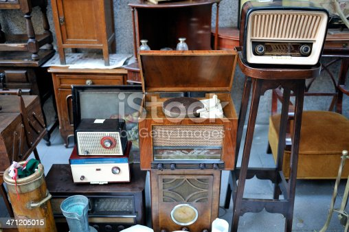 Flea market stall with obsolete radio equipment and record player.