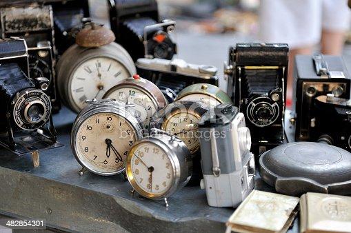 Flea market stall with old camaras and clocks.