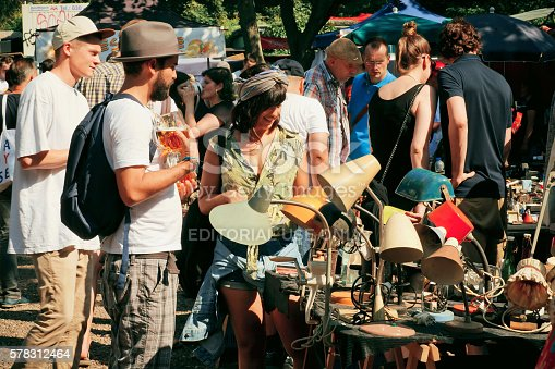 Berlin, Germany - August 30, 2015:  Flea market with young people choosing vintage lamps and furniture on August 30, 2015. Urban area of Berlin comprised 4 million people, 7th most populous in EU