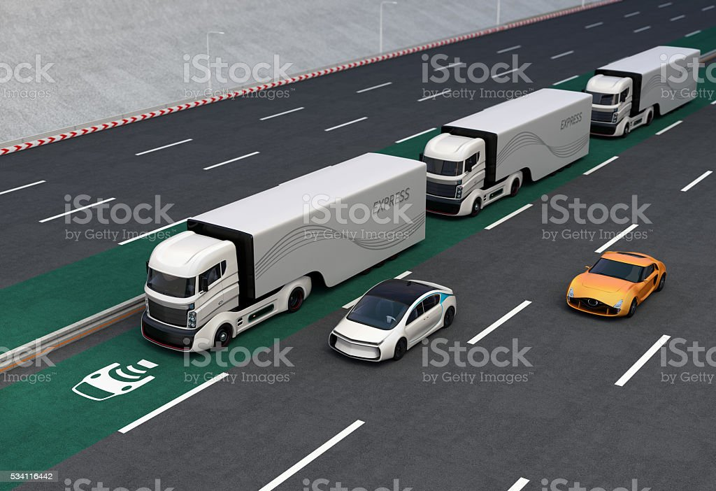 Fleet of autonomous hybrid trucks driving on wireless charging lane stock photo