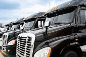 istock Fleet of black 18 wheeler commercial semi-trucks 1127374749