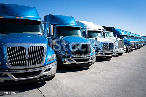 istock Fleet of blue 18 wheeler semi trucks 928695870