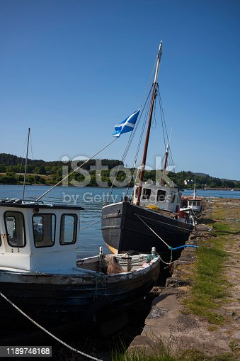A fleet of old, wooden, fishing vessels docked on a pier along Broadford Bay in Broadford, Isle of Skye, Scotland, United Kingdom.