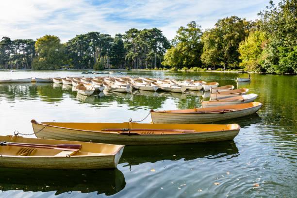 Une flotte de bateaux à rames location liée à un autre à la fin de la journée sur le lac inférieur du Bois de Boulogne à Paris. - Photo