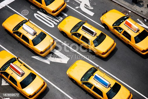 Fleet of yellow taxi cabs make their way down the street of Broadway in New York City in view from above