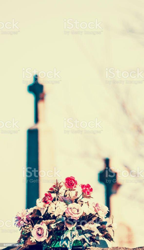 Fleurs artificielles et croix stock photo