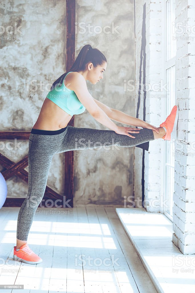 Side view of beautiful young woman in sportswear stretching out her...