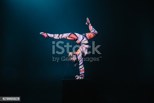 629965740 istock photo Flexible blonde circus acrobat doing equilibre balance handstand 629965628